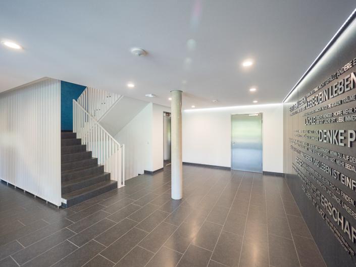 Blick in das Treppenhaus und auf den Fahrstuhl im Erdgeschoss